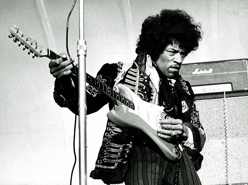 Image of Jimi Hendrix playing an electric guitar upside down to account for his left-handedness.